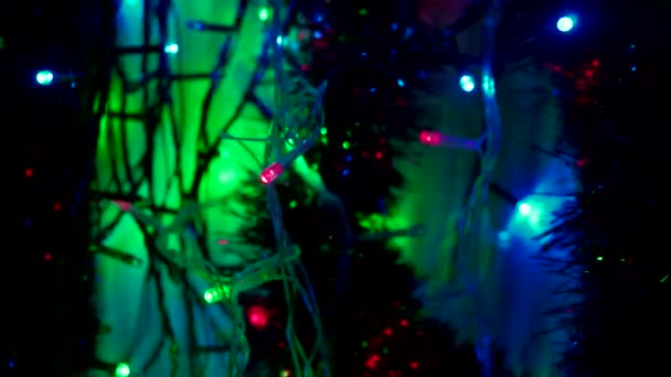 Színes karácsonyi bokeh villogó színes neonfényekkel. Absztrakt homályos háttér zökkenőmentesen és élesen villogó újévi rózsaszín kék és zöld piros fények. Villogó színes felvételek 4K
