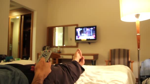 young man watching tv in hotels room