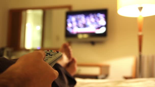 young man using tv in hotels room, feet in hotel