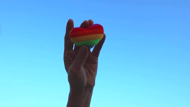 Lgbt flag rainbow heart shape LGBT day concept, hand holds a heart painted like a LGBT flag, silhouetted against blue sky