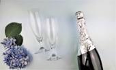 festlicher Hintergrund mit Blumen, Sektflasche und Flöten