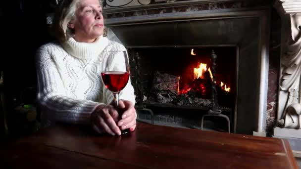 single aged woman in a white sweater drinking red wine in front of a burning fireplacelonely aged woman drinks red wine in front of a burning fireplaceolder senior woman drinks red wine at home