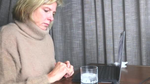 Kranke Frau hat die Grippe oder Erkältungssymptome und bläst ihre Nase, während eine Arbeit am Computer. sie hat eine Erkältung. Nahaufnahme der kaukasischen Frau niesen und trinkt Wasser mit Medizin.
