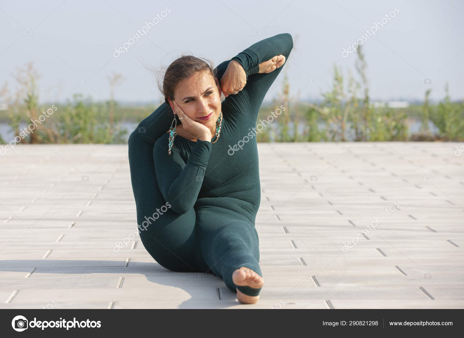 Thin Brunette Girl Plays Sports And Performs Beautiful And Sophisticated Yoga Poses In A Summer Park Stock Photo C Biggur 290821298