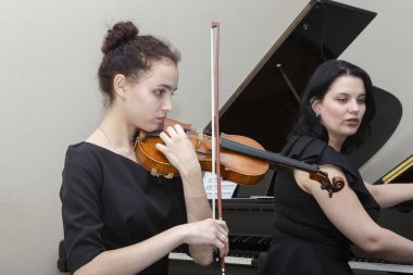 Musicians of the symphony orchestra. A young violinist and cellist play, the pianist accompanies them.