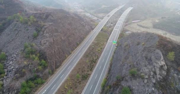 A híd keresztül száraz hegyi autópálya emelkedett légifelvételek. Autópálya, át a hegyen, az autók és teherautók vezetés mindkét irányban. Open road, autópálya, száraz környezetben. Chengde, Kína.