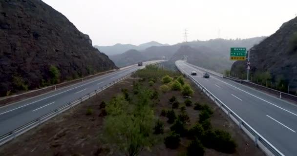 Letecký pohled na dálnici s mostem přes horské. Dálnice přes hory s osobní a nákladní automobily i směr jízdy. Otevřené silnice, dálnice v suchém prostředí. Chengde, Čína.
