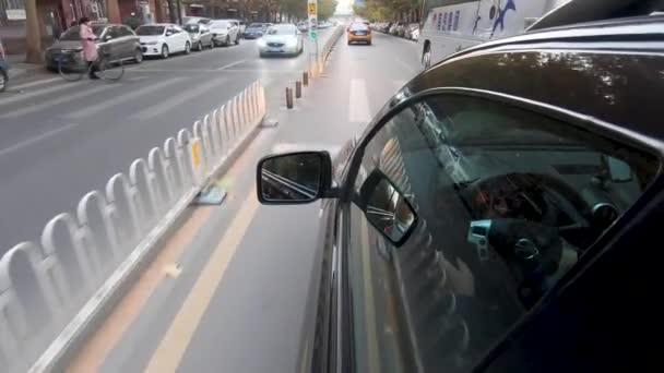 Řízení z bokorysu auta s odrazem na okno a řidič v autě. Boční kamera na auto během znečištěné den na cestě z města v Pekingu, Čína.