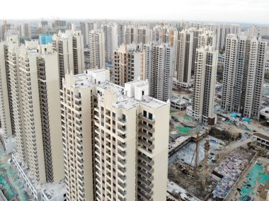 Aerial view of massive building sites in construction with tower crane. Building blocks apartment in construction in developing part of the city of Tianjin in China. Estate construction  site.