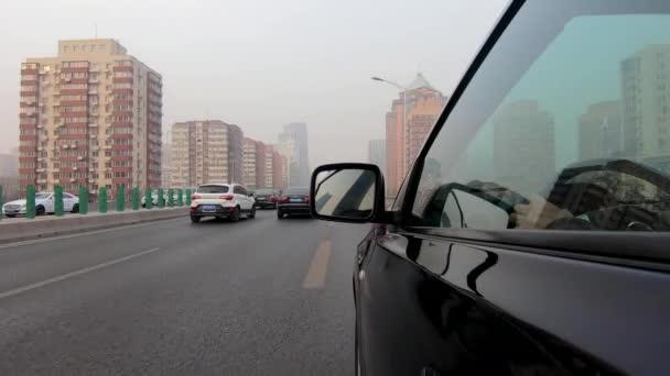 Fahransicht von der Seite des Autos mit Reflexion des Fensters und des Fahrers im Auto. Seitenkamera am Auto während des verschmutzten Tages auf der Straße der Stadt Peking, China.