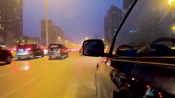 Time-Lapse Fahransicht aus Seitenansicht des Autos mit der Reflexion über die Fenster und Fahrer im Auto. Seitenkamera auf Mietwagen in Beijing City, China während der Nachtzeit