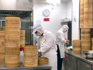 Chefs are cooking Chinese dumplings by the traditional bamboo steamers in a restaurant. Dim Sum chefs working wrapping dumplings at famous restaurant Din Tai Fung. Beijing, China. 09/10/2018