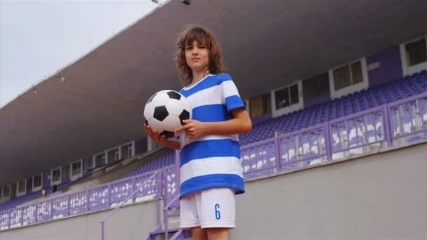 Zpomalený pohyb mladého chlapce s fotbalovým míčem fotbalového stadionu, 4k