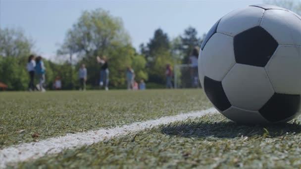 Gyerekek játszanak egy játszótéren, egy labda közel elöl, 4k