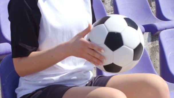 Mladá žena fotbalista sezení s fotbalovým míčem na stadionu, 4k