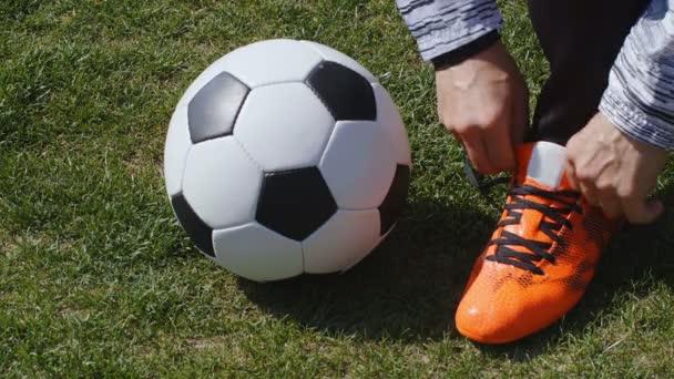 Fotbal, fotbal. Profesionální fotbalista přezka jeho červené boty před tréninkem, 4k