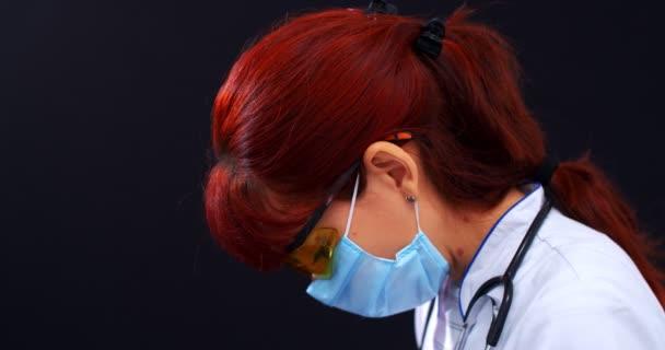 COVID-19 Gesundheitskonzept. Seitenansicht einer Ärztin mit Maske und Schutzbrille auf schwarzem Hintergrund. Sie blickt in die Kamera. 4k Zeitlupe