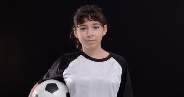 Portrét dospívající dívky fotbalista s fotbalovým míčem na černém pozadí, 4k