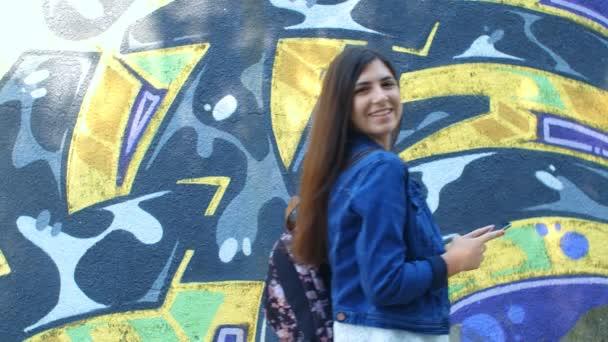 Csinos kaukázusi lány okostelefonnal a kamera előtt. Kültéri fal graffitivel a háttérben. 4k, lassított mozgás 75fps