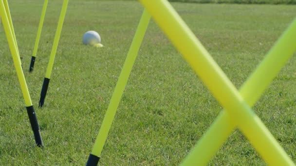 Foci mozgékonysági edzés felszerelés. Profi futball fiatal női játékos mozgékonysági pólusokkal. 4k