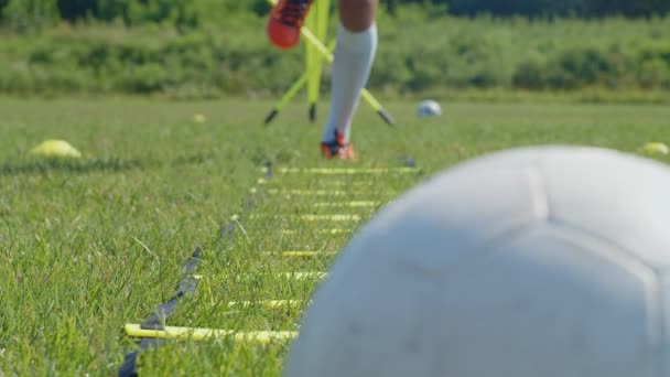 Detail shot of a football young man player legs with an agility ladder. 4k