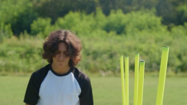 Portrait of young footballer soccer player with a ball by agility poles. 4k slow motion