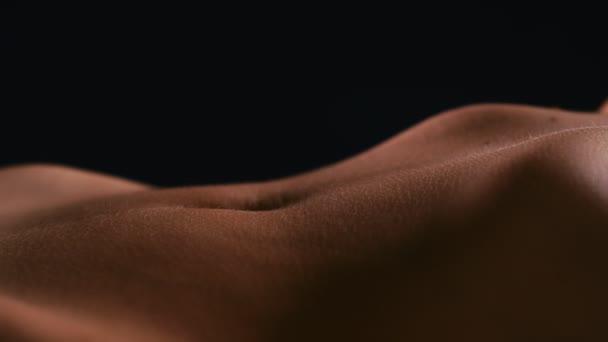 Nahaufnahme eines nackten weiblichen Bauches auf schwarzem Hintergrund, 4k