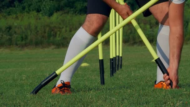 Soccer player putting poles preparing for the training on a field, 4k slow motion
