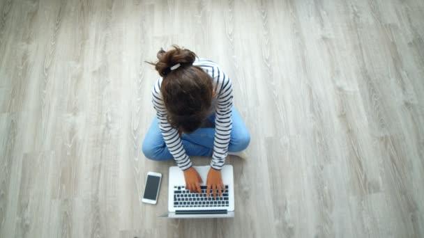 Mladá dívka pracující na notebooku na podlaze doma, 4k pohled shora