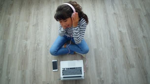 Mladá dívka se sluchátky pomocí laptopu poslech hudby a tance na podlaze doma, 4k horní pohled