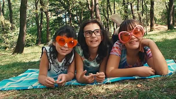 Pan of three girlfriends faces with funny sunglasses laying in the park. 4k