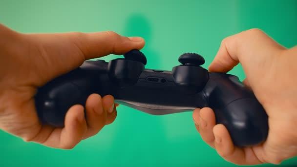 Gamepad a játékos kezében szemben a nagy síkképernyős, zöld képernyős, 4k