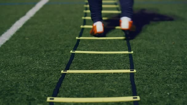 Soccer agility training equipment. Professional football player with agility ladder at night. 4k slow motion