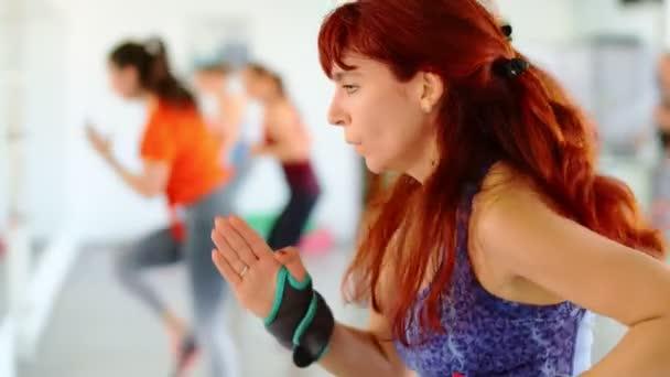 Dance fitness Zumba osztály csoport gyönyörű nők táncolnak élvezi edzés gyakorló koreográfia mozog egy oktató egy fitness stúdió, 4k lassított felvétel