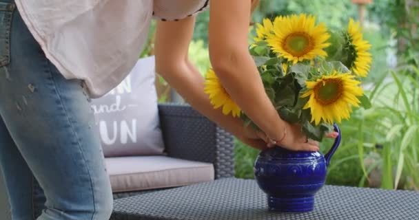 A woman arranging a bouquet of beautiful yellow sunflowers in a vase in a green garden, 4k
