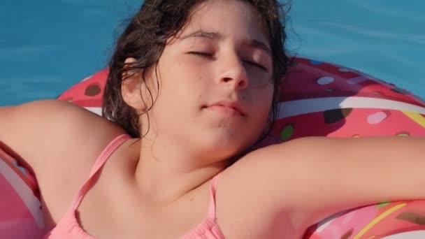 11-12 Jahre alte fröhliche süße kaukasische Mädchen auf einem aufblasbaren Donut-Kreis im Schwimmbad in einem Garten liegend. Kühle Sommerferien für Kinder und Jugendliche. Spiele auf dem Wasser. Pinkfarbene Spenden. 4k Zeitlupe