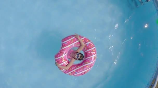 Glückliche kleine kaukasische Kinder, die sich in einem Schwimmbad in einem Garten vergnügen. Ansicht von oben. Kühle Sommerferien für Kinder und Jugendliche. Spiele auf dem Wasser. Pinkfarbene Spenden. 4k