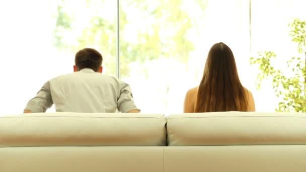 Pohled zezadu na pár odpočinku na pohovce doma a mimo zeleným pozadím při pohledu přes okno do obývacího pokoje
