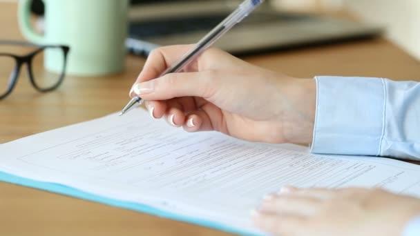 Nahaufnahme einer Frau beim Ausfüllen eines Formulars auf einem Tisch zu Hause oder im Büro