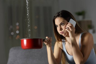 Furious woman claiming insurance for water leaks sitting on a couch in the living room at home