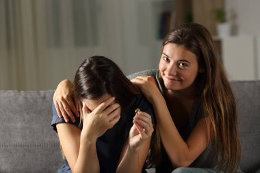 Hypocrite friend comforting a divorced wife sitting on a couch in the living room at home