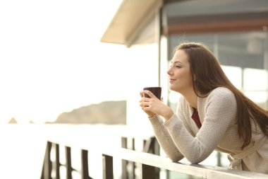 Happy hotel guest relaxing drinking coffee looking away on vacation