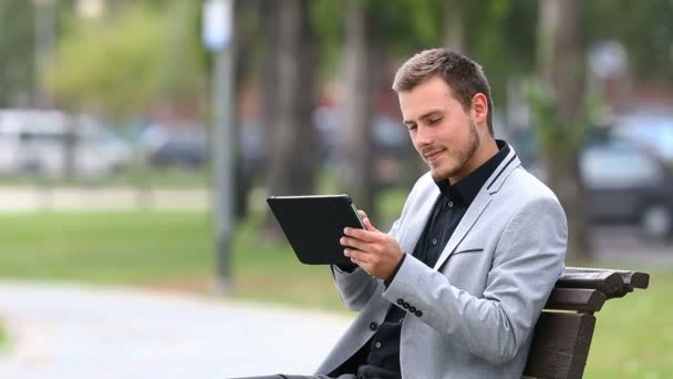 Businessman reads bad online news in a tablet and complaints sitting on a bench in a park