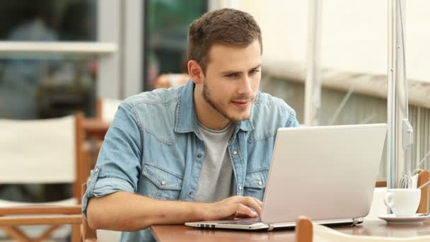 Excited man reading good news in a laptop in a coffee shop