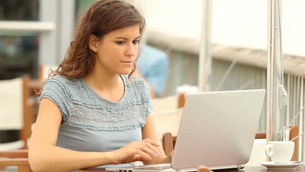 Excited woman reading good news in a laptop in a coffee shop