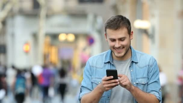 Front view of a man walking and using a smart phone in the street