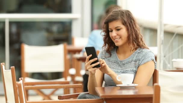 Happy woman checking a smart phone in a coffee shop in a rainy day