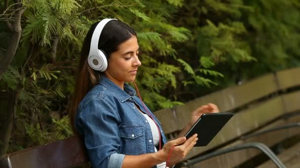 Happy woman wearing headphones watching online videos in a tablet sitting on a bench in a park