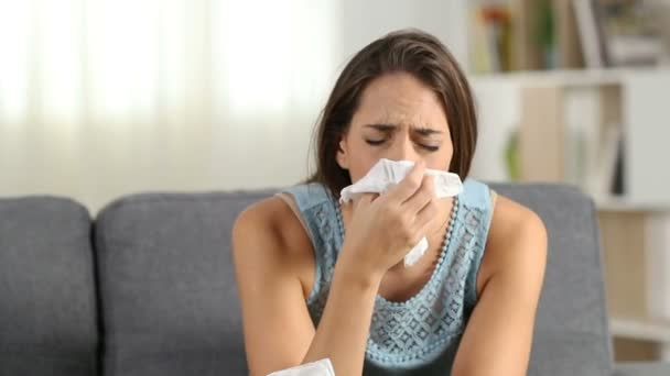 Ill woman blowing mucus and sneezing in a wipe suffering flu symptoms sitting on a sofa at home in winter