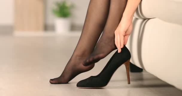 Close up of a woman hand putting on high heel shoes and walking at home